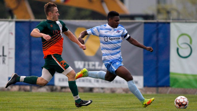 Lansing United's DeJuan Jones, right, gets past the Michigan Bucks' Nick Norman on a breakaway on May 12, 2018, in East Lansing. Jones leagues United with four goals this season.