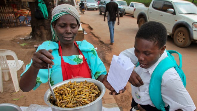 "In this photo taken Friday, Nov. 25, 2016, market-seller Sylvia Namwanje, left, sells edible grasshoppers to a student at her stall in the Kamwokya district of the capital Kampala, in Uganda. Grasshoppers, known in the local Luganda language as ""nsenene,"" are a delicacy among millions in this East African during the rainy season. Fried grasshoppers have become a lucrative trade and businesses around the nation are making the most of the demand for the crunchy critters."