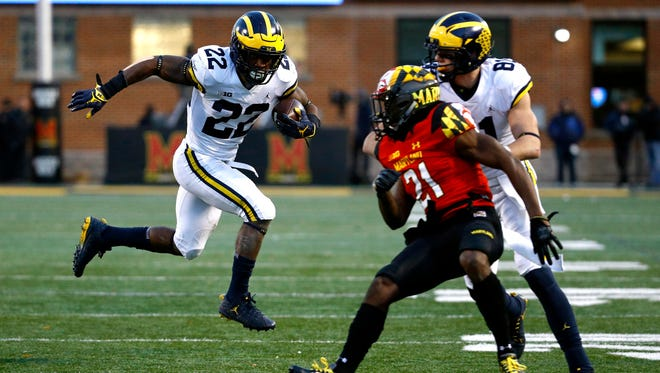 Michigan running back Karan Higdon, left, rushes past Maryland defensive back RaVon Davis (21) and Michigan wide receiver Nate Schoenle in the first half on Saturday, Nov. 11, 2017, in College Park, Md.