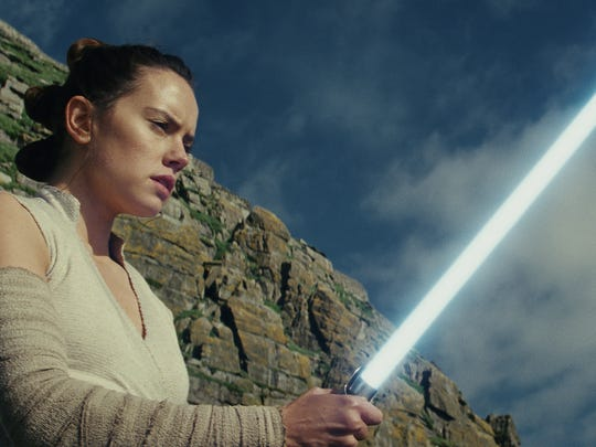 Rey (Daisy Ridley) wields a mean lightsaber in 'Star Wars: The Last Jedi.'