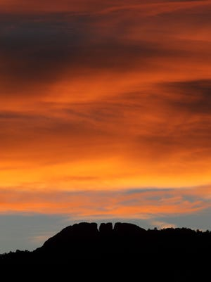 The setting sun lights up the clouds that loom over Horsetooth Rock Sept. 30, 2013.
