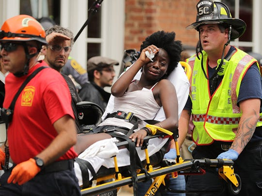 "Rescue workers move victims on stretchers after car plowed through a crowd of counter-demonstrators marching through the downtown shopping district Aug. 12, 2017, in Charlottesville, Virginia. The car plowed through the crowed following the shutdown of the ""Unite the Right"" rally by police after white nationalists, neo-Nazis and members of the ""alt-right"" and counter-protesters clashed near Lee Park, where a statue of Confederate General Robert E. Lee is slated to be removed."