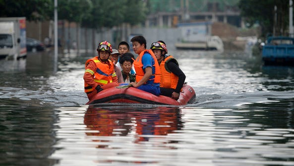 In this July 21, photo, rescuers use a raft to transport