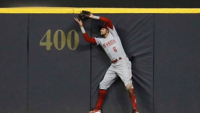 Cincinnati Reds' Billy Hamilton makes a catch at the wall of a ball hit by Milwaukee Brewers' Domingo Santana during the sixth inning of a baseball game Monday, April 16, 2018, in Milwaukee.