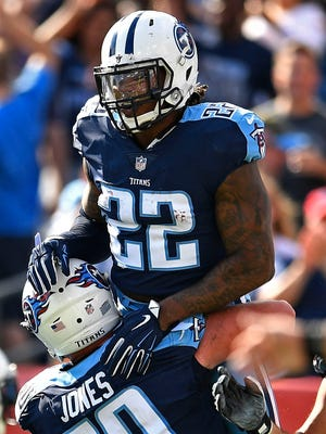Titans center Ben Jones (60) raises running back Derrick Henry (22) in the air after he scored in the first half Sunday.