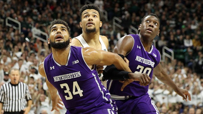 Michigan State's Kenny Goins fights for position with Northwestern's Sanjay Lumpkin and Scottie Lindsey (20) during their game on Dec. 30 at Breslin Center. Goins, a 6-foot-6 former preferred walk-on who found a niche defending stretch forwards, has been forced to play center this season.