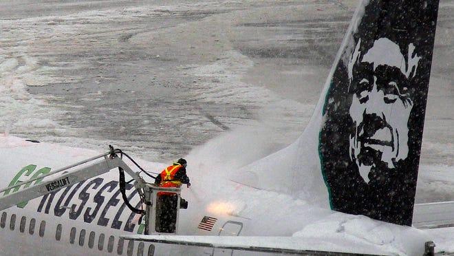 An Alaska Air plane is de-iced at Newark Liberty International Airport on Monday, Feb. 3, 2014.