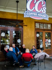 A group of patrons converse at CC's Coffee House in