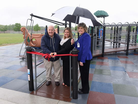 Fundraising coordinator John Bowden, assistant principal Nicole Hansen and principal Kate Flynn cut a ribbon for the new adaptive playground at Talahi Community School Tuesday, May 23, in St. Cloud. Hansen has since become Talahi's principal.