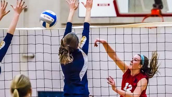 Taylor Delbridge (right) of Mason hits through a Portage Central block during their Class A regional semifinal match last Tuesday.
