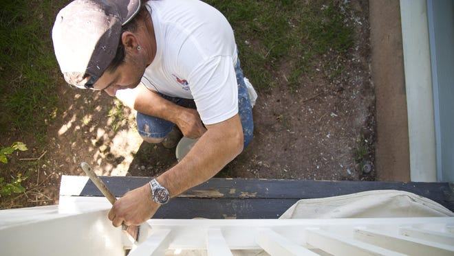 Joe Fernandez paints the front porch railing at C.M. Russell's original residence Monday. Restorations include painting the house, re-shingling the roof and improving the historical accuracy of the interior.