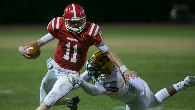 Brophy's Cade Knox (11) breaks a tackle from Mountain Pointe's Bruce Hester (56) on a long-run at Arizona Phoenix College in Phoenix, Arizona, on Friday, Oct. 10, 2014.