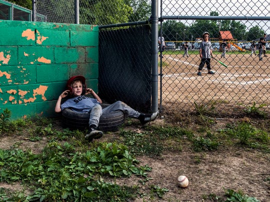 Jamison Heitger fights off boredom as he waits for his turn to bat during his last little league baseball game of the season at Scott Baseball field in Scott Township on June 5, 2017.