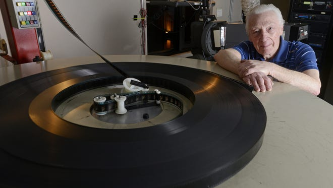"""Clarence """"Pat"""" Patterson poses with one of the platters that feeds film to a projector at the West Mall 7 Theatre."""