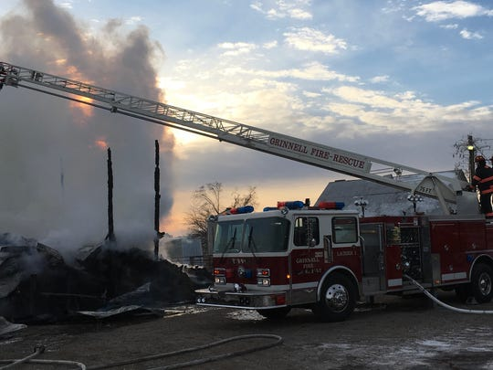 Grinnell fire fighters use an aerial ladder fire truck to extinguish a barn fire north of Grinnell early Wednesday morning, Dec. 14.