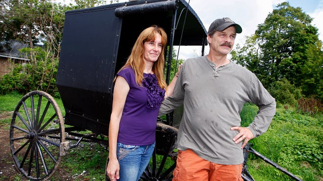 Jeffrey M. and Pamela L. Stinson stand by a buggy in front of their Bigelow home. Two Amish girls who were abducted Aug. 13 showed up at the Stinsons' home the next night, prompting the couple to drive the girls back to their Heuvelton home.