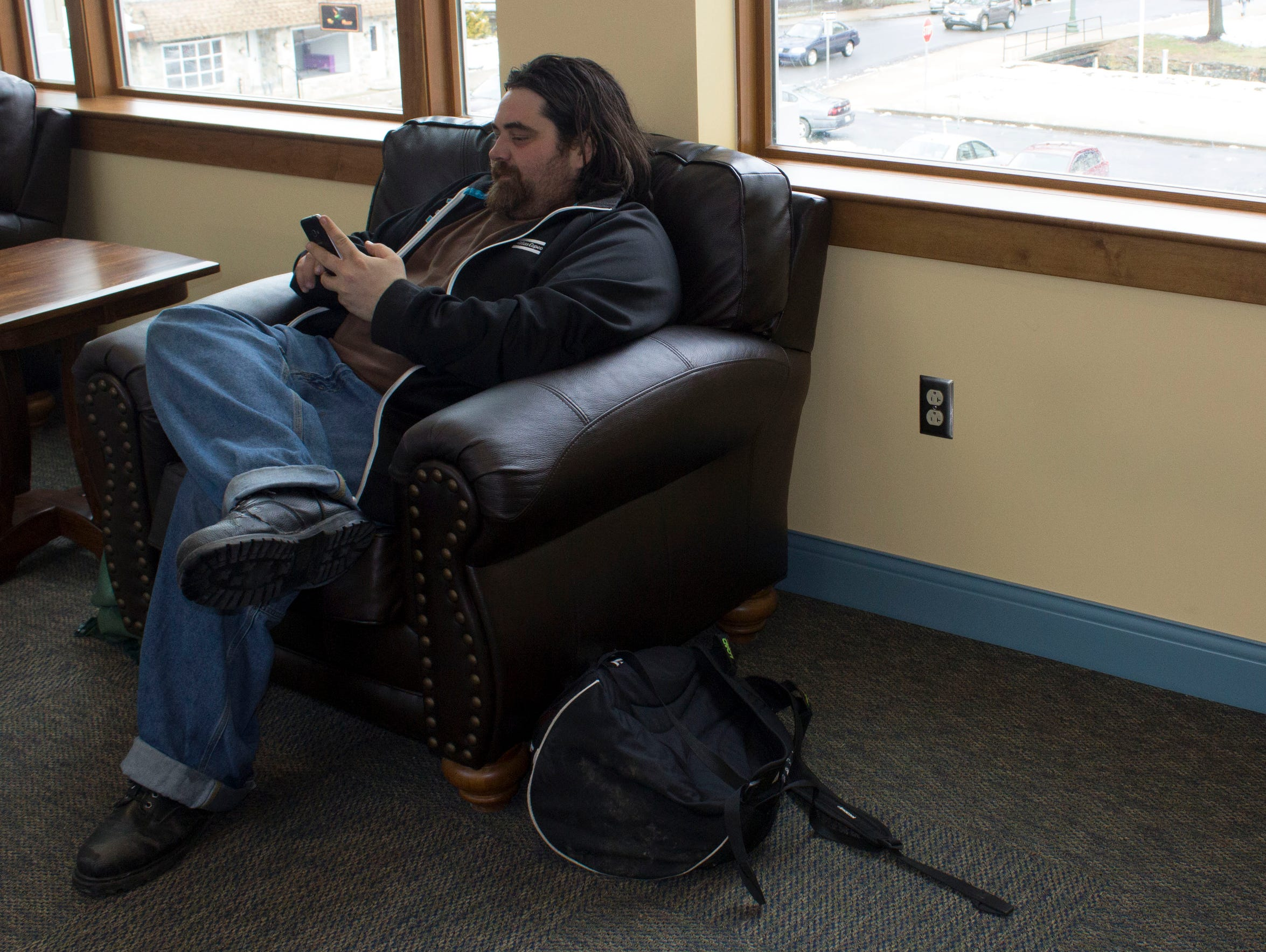 Jason Davies, 34, sits on a chair and plays on his