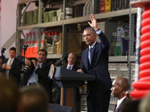 President Barack Obama waves to employees of Cedar