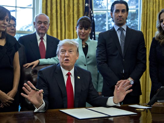 "WASHINGTON, DC - JANUARY 30: (AFP OUT) U.S. President Donald Trump speaks before signing an executive order surrounded by small business leaders in the Oval Office of the White House January 30, 2017 in Washington, DC. Trump said he will ""dramatically"" reduce regulations overall with this executive action as it requires that for every new federal regulation implemented, two must be rescinded. (Photo by Andrew Harrer - Pool/Getty Images)"