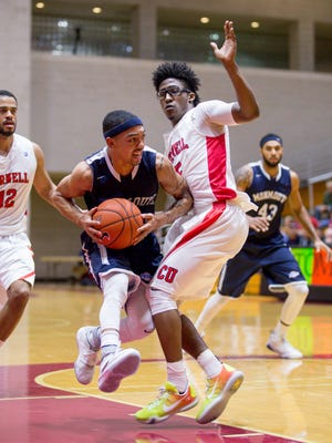 Monmouth point guard Justin Robinson attempts to dribble past Cornell point guard Robert Hatter during Wednesday's game in Newman Arena in Ithaca. Monmouth defeated Cornell 78-69.