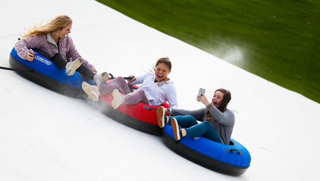 Kaitlyn Bennett (left), Sarah White (middle), and McKenzi Marsch ride tubes down the Snowflex tubing hill at Wolfe Mountain on Friday, Dec. 1, 2017. The new 400-foot tubing hill is a year-round addition to Branson Zipline.