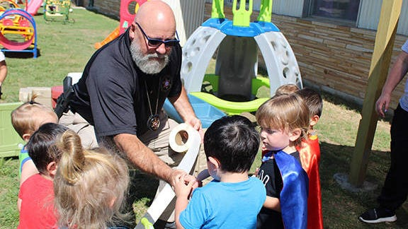 Washington County Sheriff's Investigator Herb Cline hands out gold sheriff's badge stickers to two-year-olds at Safe Haven Child Development Center on Tuesday. Kim Archer/Examiner-Enterprise