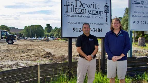 Chris Tilton, co-principal of Dewitt Tilton Group, left, stands with R. Daniel Blanton Jr., co-owner of Mint Car Wash on the construction site of the new Mint Car Wash building at 302 Commercial Dr.