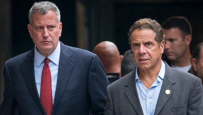 In this photo from Sunday, Sept. 18, 2016, New York Mayor Mayor Bill de Blasio, left, and  Gov. Andrew Cuomo walk near the scene of an explosion in Manhattan's Chelsea neighborhood, in New York. Mayor Bill de Blasio cruised to a second term in November 2017, but a feud with fellow Democrat Gov. Andrew Cuomo continues.