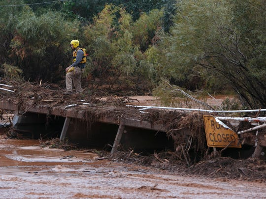 A search and rescue team member keeps on eye on the flood waters in Short Creek as it flows past him as he stands near the intersection of Arizona and Central streets in Colorado City Tuesday, Sep. 15, 2015.