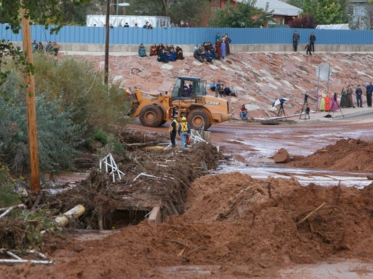 Residents of the town towns of Hildale and Colorado City look on as efforts to remove debris at the intersections of Arizona and Central streets in Colorado City continue Tuesday, Sep. 15, 2015. Search and rescue personnel are still looking for five people missing after flash floods swept through the area on Monday.