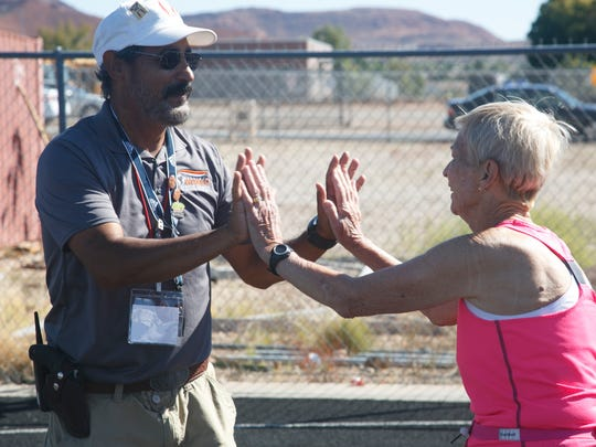 Dottie Gray gets high fives from track official Robert