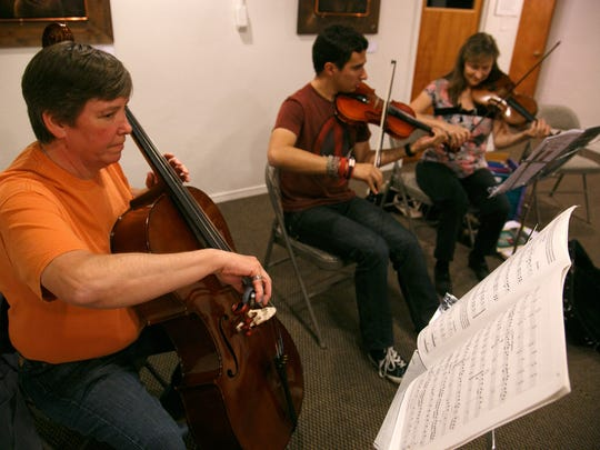 Jane Brennan, left, plays the cello with the New Horizons Orchestra, during a rehearsal at the DiFiore Center in St. George Tuesday, Nov. 3, 2015.