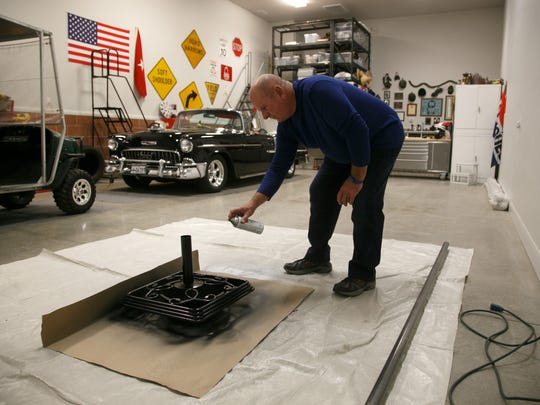 John Hansen spray paints a flag stand as he works in