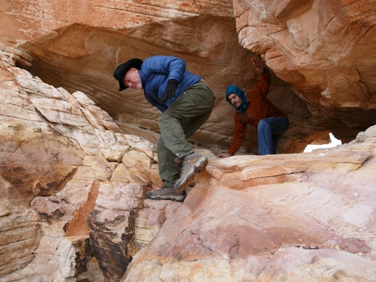 Friends of Gold Butte board member Byron George, left, and Steve Kiggins, the Spectrum & Daily News' executive editor, scramble through a small arch at the Falling Man Petroglyph site in the Gold Butte Area of Critical Environmental Concern Friday, Jan. 15, 2016.