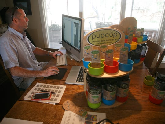Andy Green works on his computer while surrounded by displays for his companies Pupcup dog water bowls Thursday, March 17, 2016.