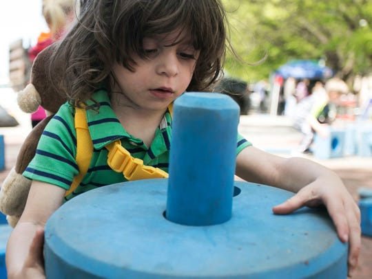 Rylan Brent, 2, of Dover, plays in the kids zone Saturday,