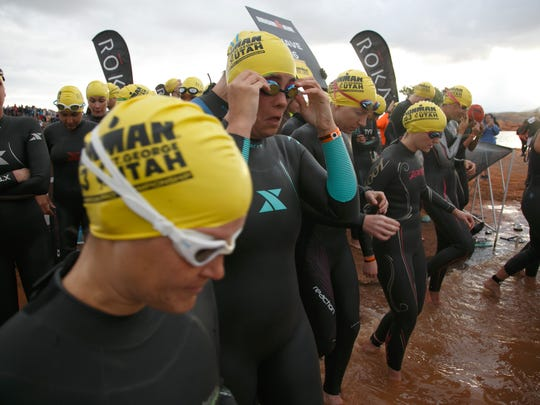 Ironman 70.3 St. George participants, including the Spectrum & Daily News' Casie Forbes, at center, enter the waters of Sand Hollow Reservoir prior to the start of their start wave Saturday, May 7, 2016.