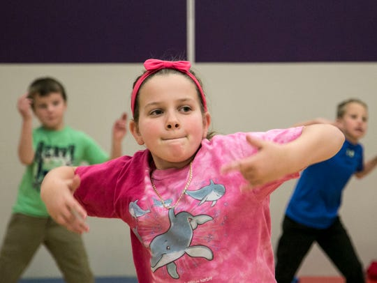 Third-grader Maya Cook, dances along with Artist In