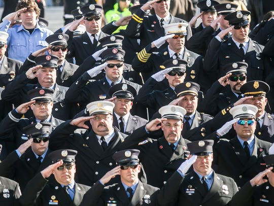 Out of town firefighters salute, as Lt. Dennis H. DeVoe