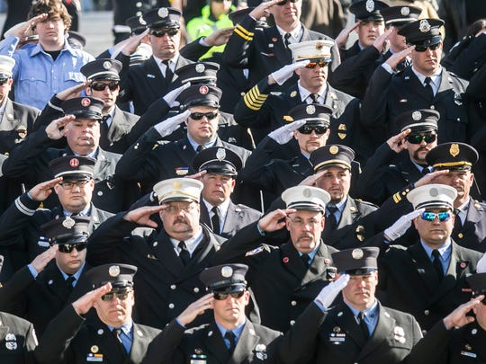 Out of town firefighters salute, as Lt. Dennis H. DeVoe Funeral Procession passes in front of the Pennsylvania State Capital Friday March 17, 2017, in Harrisburg. Amanda J. Cain photo