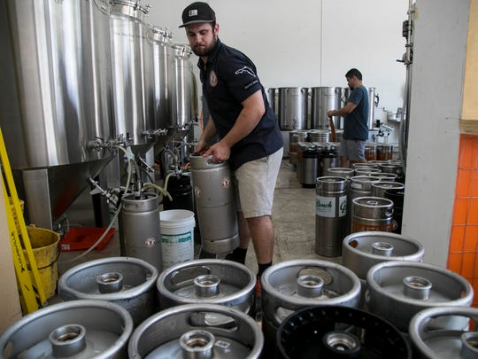 Tom Gambino fills kegs at Momentum Brewhouse on Tuesday,