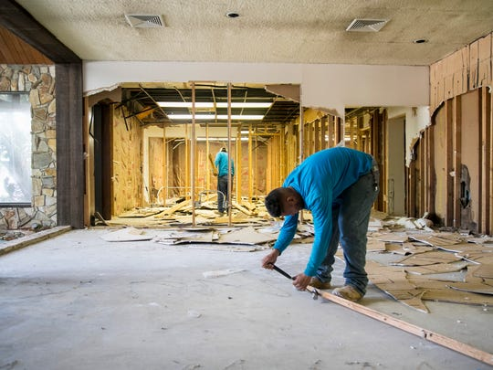 Workers demolish the interior walls of the Michigan Homes building to create an open space for the Haus of Trikes & Bikes showroom.