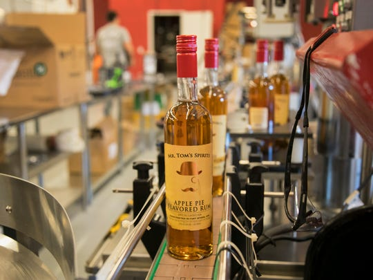 Bottles of Mr. Tom's Spirits Apple Pie Flavored Rum move on the conveyor belt after being filled on Thursday, January 4, 2017, at List Distillery in Fort Myers.