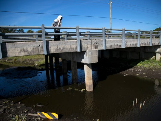 A man looks over the Billy's Creek bridge on Marsh