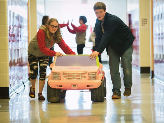 Eighth-graders Julia Kreck (left) and Nichlos Crawford at Smyrna Middle school roll a toy vehicle through the school hallway. The students are designing and modifying 6 and 12-volt battery-operated cars for children with disabilities.