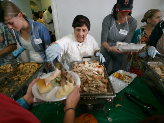 Volunteers serve community members at the Red Rock Canyon School's annual community Thanksgiving dinner Thursday, Nov. 27, 2014.