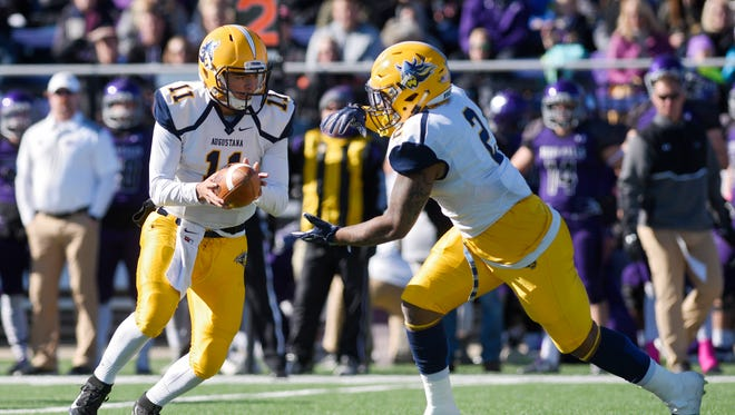 Augustana quarterback Kyle Saddler (11) hands the ball off to running back Ryan Bardberry (2) during the first half of their NCAA DII game at Bob Young Field in Sioux Falls on Saturday, Oct. 28, 2017.