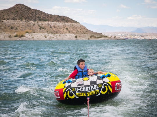 13-year-old Saxon Marr, left and 6-year-old Brenden Morris ride behind a boat on Elephant Butte Lake, July 2, 2016.