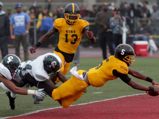 Detroit King quarterback Dequan Finn dives into the