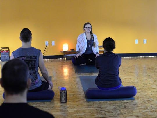 Yoga teacher Brandy Oswald speaks to participants in